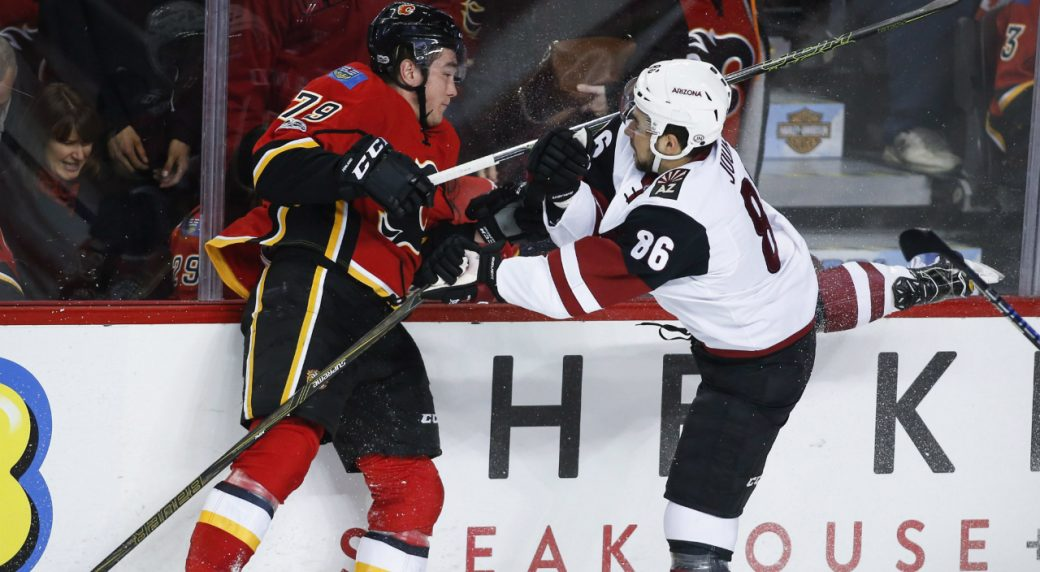 Arizona-Coyotes'-Josh-Jooris,-right,-checks-Calgary-Flames'-Micheal-Ferland-during-first-period-NHL-hockey-action-in-Calgary,-Monday,-Feb.-13,-2017.(Jeff-McIntosh/CP)