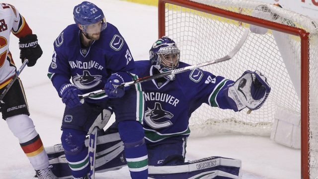 Vancouver-Canucks-goalie-Ryan-Miller-(30)-makes-a-save-near-teammate-defenceman-Alexander-Edler-(23)-against-the-Calgary-Flames-during-third-period-NHL-hockey-action-in-Vancouver-on-Saturday,-February-18,-2017.-(Ben-Nelms/CP)