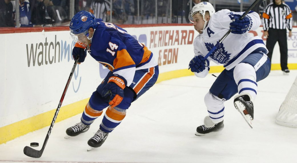 New-York-Islanders-defenceman-Thomas-Hickey-(14)-takes-control-of-the-puck-in-front-of-Toronto-Maple-Leafs-winger-Leo-Komarov,-right,-of-Estonia-during-the-third-period-of-an-NHL-hockey-game,-Sunday,-Oct.-30,-2016,-in-New-York.-The-Islanders-defeated-the-Maple-Leafs-5-1.-(Kathy-Willens/AP)