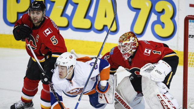 New-York-Islanders'-Anders-Lee,-centre,-is-knocked-to-the-ice-by-Calgary-Flames'-Mark-Giordano,-left,-as-goalie-Brian-Elliott-looks-on-during-third-period-NHL-hockey-action-in-Calgary,-Sunday,-March-5,-2017.-(Jeff-McIntosh/CP)