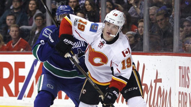 Calgary-Flames-left-wing-Matthew-Tkachuk-(19)-plays-the-puck-near-Vancouver-Canucks-defenceman-Christopher-Tanev-(8)-during-first-period-NHL-hockey-action-in-Vancouver-on-Saturday,-February-18,-2017.-(Ben-Nelms/CP)