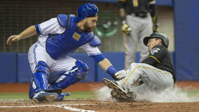 Pittsburgh-Pirates'-Adam-Frazier,-right,-is-tagged-out-at-home-by-Toronto-Blue-Jays-catcher-Russell-Martin-during-fifth-inning-pre-season-MLB-baseball-action,-in-Montreal-on-Friday,-March-31,-2017.-(Paul-Chiasson/CP)