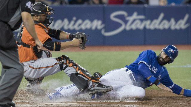 Toronto-Blue-Jays'-Jose-Bautista-scores-getting-his-foot-on-home-plate-before-Baltimore-Orioles-catcher-Welington-Castillo-can-come-down-with-the-tag-in-the-seventh-inning-of-AL-baseball-action-in-Toronto-on-Saturday-April-15,-2017.-(Fred-Thornhill/CP