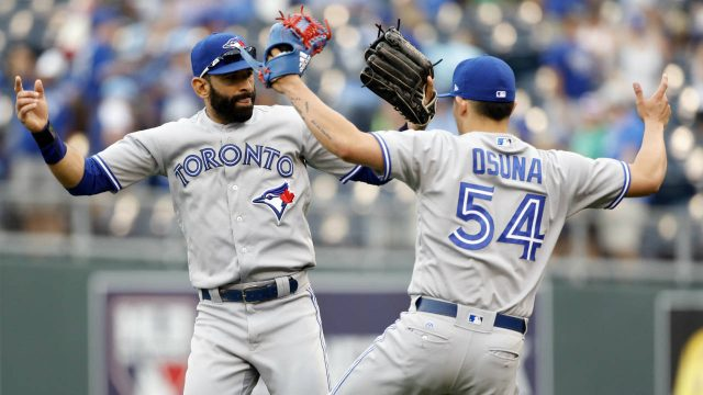 Toronto-Blue-Jays'-Jose-Bautista,-left,-and-pitcher-Roberto-Osuna,-right,-celebrate-at-the-end-of-a-baseball-game-against-the-Kansas-City-Royals-at-Kauffman-Stadium-in-Kansas-City,-Mo.,-Sunday,-June-25,-2017.-(Colin-E.-Braley/AP)