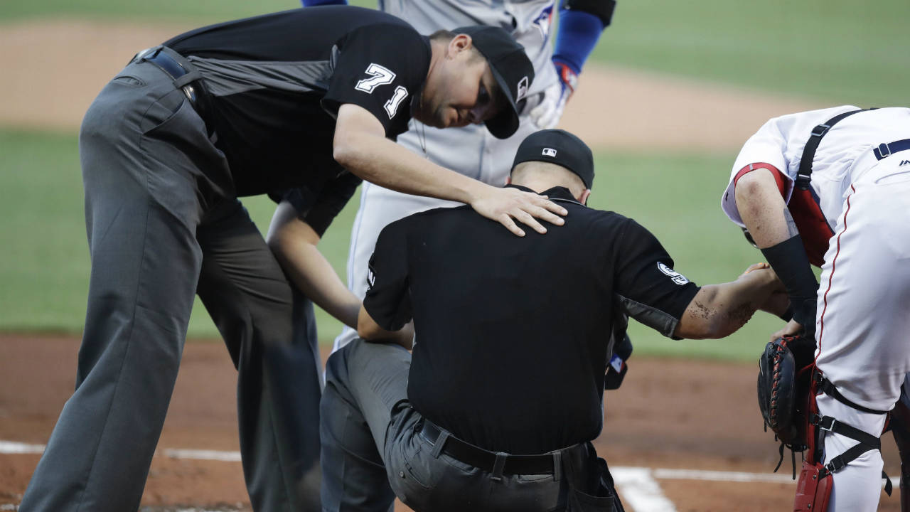 Second-base-umpire-Jordan-Baker-(71)-rests-his-hand-on-home-plate-umpire-Chris-Segal,-after-Segal-was-accidentally-hit-on-the-head-by-Toronto-Blue-Jays'-Josh-Donaldson's-bat-during-the-first-inning-of-a-baseball-game-against-the-Boston-Red-Sox-at-Fenway-Park-in-Boston,-Monday,-July-17,-2017.-(Charles-Krupa/AP)