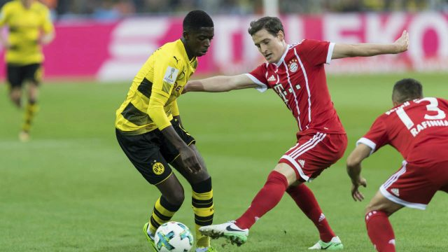 Dortmund's-Ousmane-Dembele,-left,-and-Bayern's-Sebastian-Rudy-vie-for-the-ball-during-the-Supercup-soccer-final-between-FC-Bayern-Munich-and-Borussia-Dortmund-in-the-Signal-Iduna-Park-in-Dortmund,-Germany,-Saturday,-Aug.-5-2017.-(Marius-Becker/dpa-via-AP)