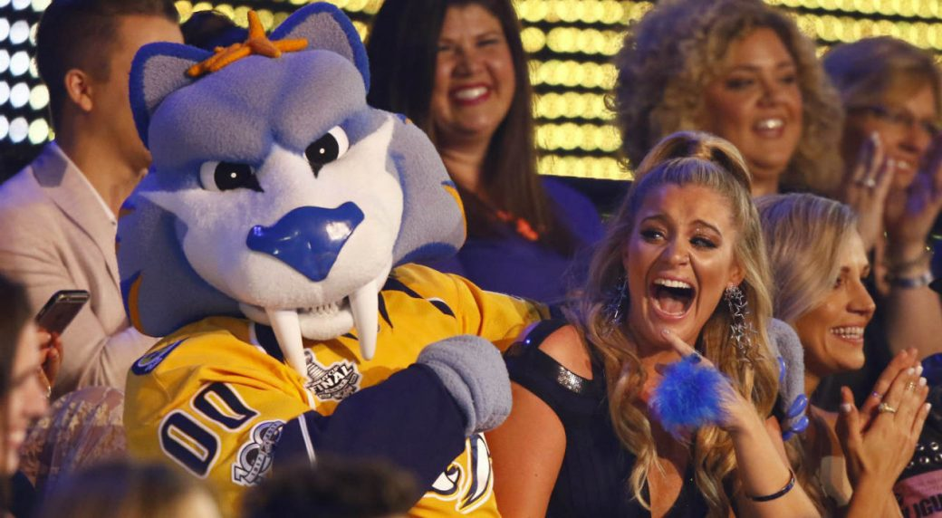 Lauren-Alaina-sits-in-the-audience-with-Gnash,-the-mascot-for-the-NHL's-Nashville-Predators.-(Photo-by-Wade-Payne/Invision/AP)