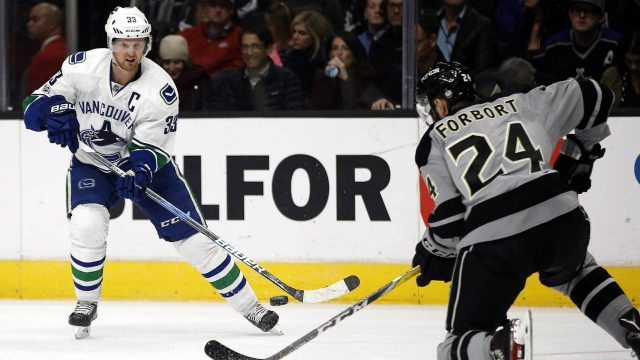 In-this-Saturday,-March-4,-2017,-file-photo,-Vancouver-Canucks-center-Henrik-Sedin,-left,-of-Sweden,-passes-the-puck-against-Los-Angeles-Kings-defenseman-Derek-Forbort-during-the-first-period-of-an-NHL-hockey-game-in-Los-Angeles.-The-NHL-will-play-its-first-games-in-China-this-fall-when-the-Kings-and-Canucks-meet-in-Beijing-and-Shanghai.-(Alex-Gallardo,-File/AP)
