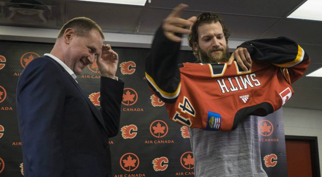 Calgary-Flames'-GM-Brad-Treliving-looks-on-as-new-goaltender-Mike-Smith-puts-on-his-jersey-at-a-news-conference-in-Calgary,-Monday,-June-26,-2017.-(Jeff-McIntosh/CP)