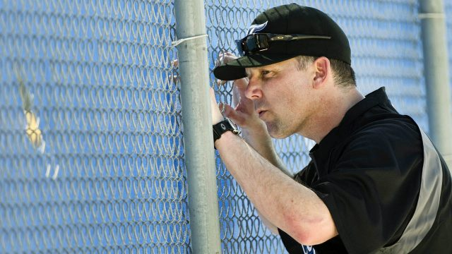 Toronto-Blue-Jays-bullpen-coach-Pat-Hentgen-peeps-through-a-hole-in-the-fence-during-baseball-spring-training-in-Dunedin,-FL,-on-Thursday,-Feb.-17,-2011.-(Nathan-Denette/CP)