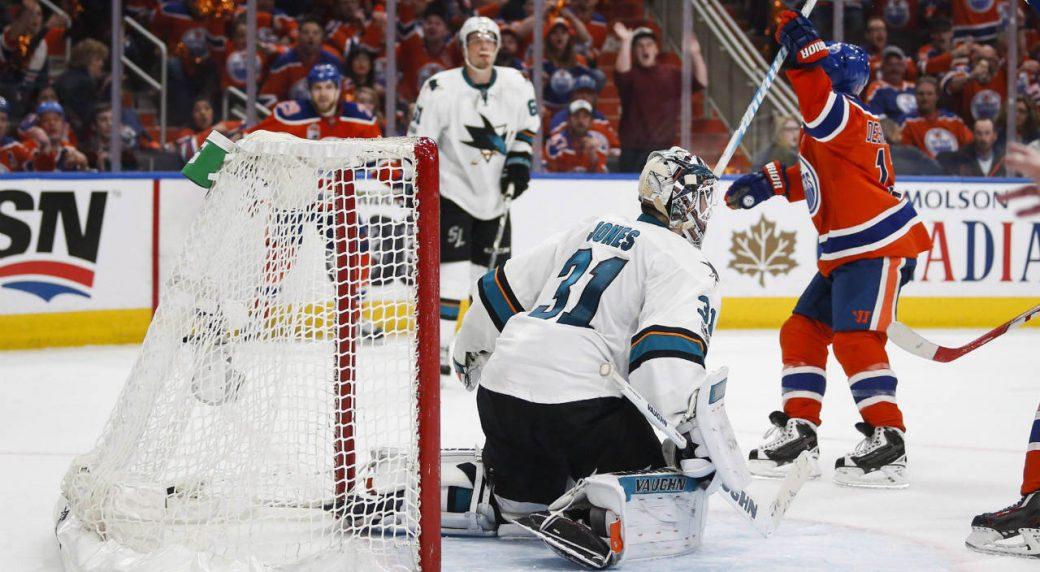 San-Jose-Sharks-goalie-Martin-Jones,-centre,-looks-on-as-Edmonton-Oilers'-David-Desharnais-celebrates-his-game-winning-goal-during-overtime-NHL-hockey-round-one-playoff-action-in-Edmonton,-Thursday,-April-20,-2017.-(Jeff-McIntosh/CP)