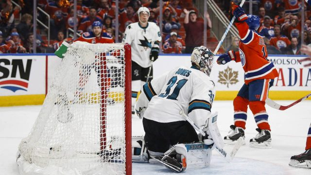 San-Jose-Sharks-goalie-Martin-Jones,-centre,-looks-on-as-Edmonton-Oilers'-David-Desharnais-celebrates-his-game-winning-goal-during-overtime-NHL-hockey-round-one-playoff-action-in-Edmonton,-Thursday,-April-20,-2017.-(Jeff-McIntosh/CP)