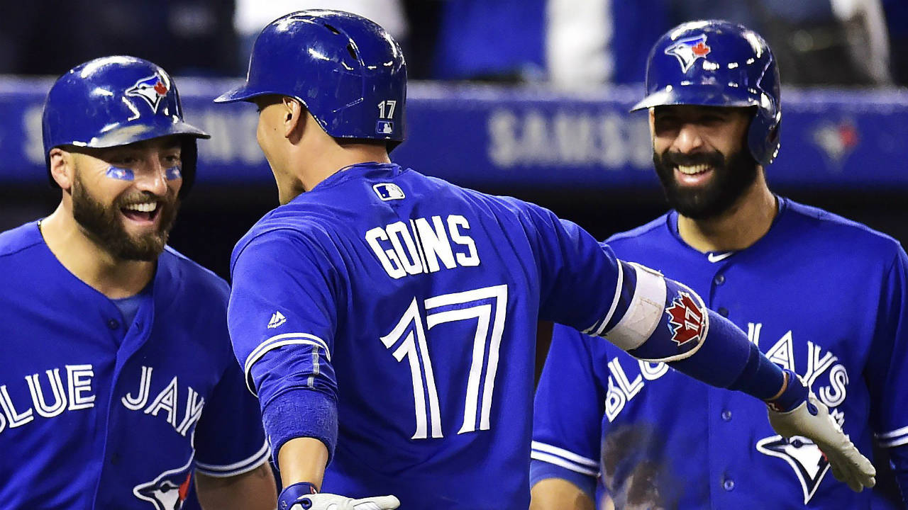 Toronto-Blue-Jays-shortstop-Ryan-Goins-(17)-is-congratulated-by-Kevin-Pillar,-left,-and-Jose-Bautista-after-hitting-a-grand-slam-against-the-New-York-Yankees-during-sixth-inning-AL-baseball-action-in-Toronto-on-Friday,-September-22,-2017.-(Frank-Gunn/CP)