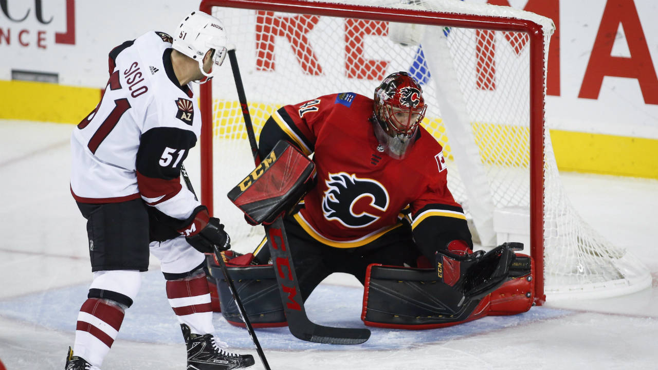Arizona-Coyotes'-Mike-Sislo,-left,-looks-on-as-Calgary-Flames-goalie-Mike-Smith-grabs-for-the-puck-during-third-period-NHL-pre-season-hockey-action-in-Calgary,-Friday,-Sept.-22,-2017.-(Jeff-McIntosh/CP)