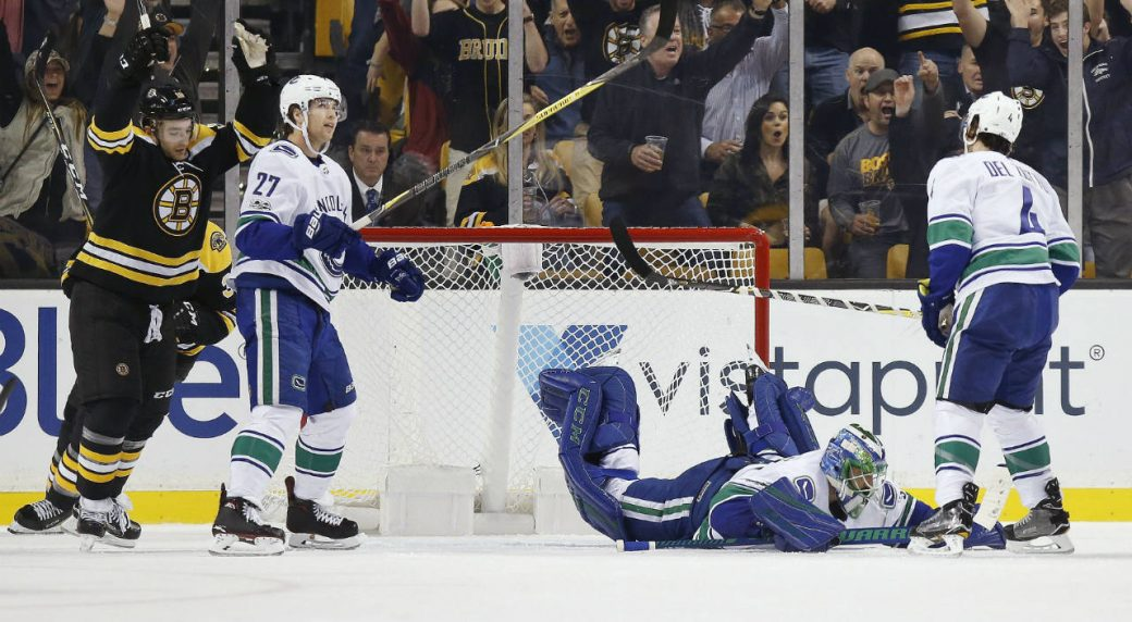 Vancouver-Canucks'-Anders-Nilsson,-second-from-right,-of-Sweden,-lies-on-the-ice-as-Boston-Bruins'-Anders-Bjork,-left,-celebrates-the-goal-by-David-Krejci-during-the-first-period-of-an-NHL-hockey-game-in-Boston,-Thursday,-Oct.-19,-2017.-(Michael-Dwyer/AP)