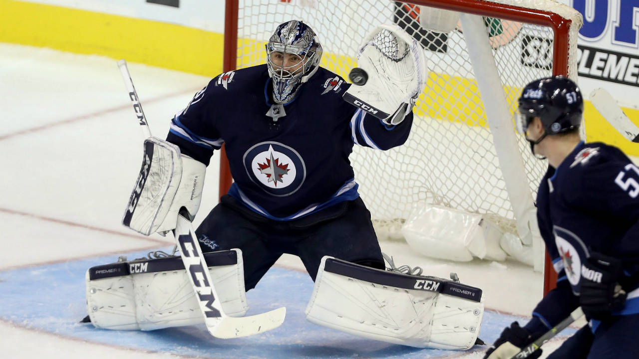Winnipeg-Jets-goalie-Connor-Hellebuyck-(37)-tries-to-make-a-glove-save-during-first-period-NHL-hockey-action-against-the-Carolina-Hurricanes,-in-Winnipeg,-Saturday,-October-14,-2017.-(Trevor-Hagan/CP)