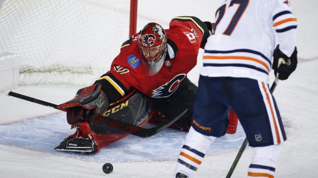 Edmonton-Oilers-forward-Milan-Lucic,-right,-has-the-puck-swatted-away-from-him-by-Calgary-Flames-goalie-Mike-Smith-during-second-period-NHL-preseason-split-squad-hockey-action-in-Calgary,-Monday,-Sept.-18,-2017.-(Jeff-McIntosh/CP)