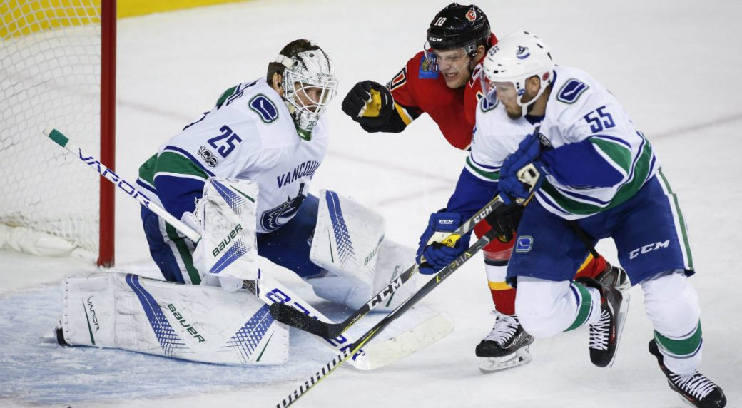 Vancouver-Canucks-goalie-Jacob-Markstrom,-left,-from-Sweden,-looks-on-as-Calgary-Flames'-Kris-Versteeg,-chases-a-lose-puck-with-Canucks'-Alex-Biega-during-first-period-NHL-hockey-action-in-Calgary,-Tuesday,-Nov.-7,-2017.-(Jeff-McIntosh/CP)