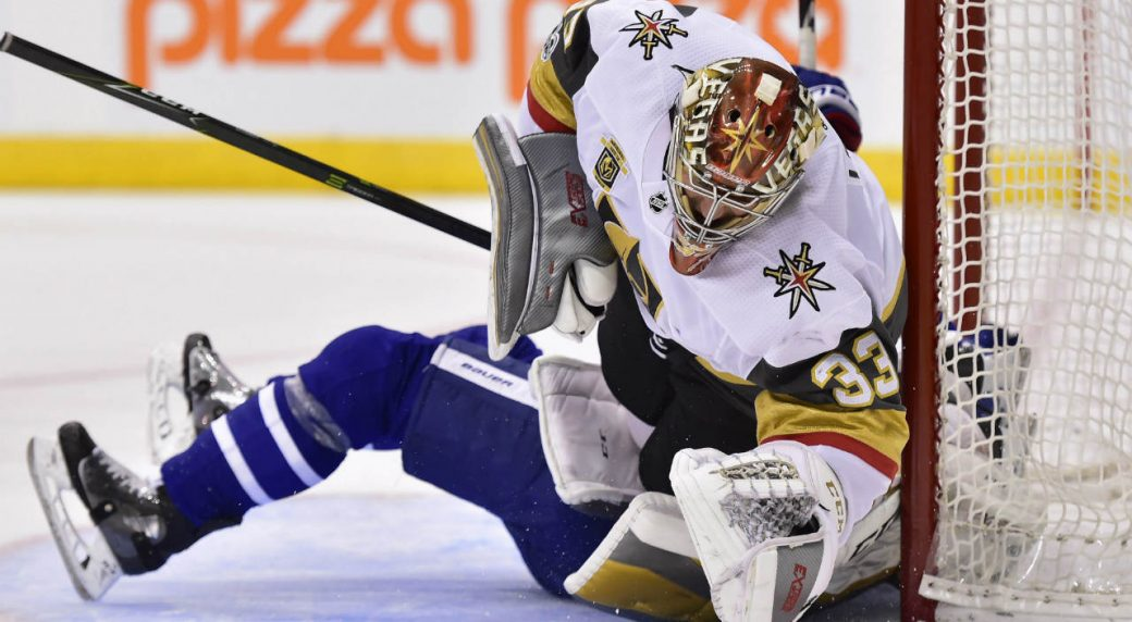 Vegas-Golden-Knights-goalie-Maxime-Lagace-(33)-is-run-over-by-Toronto-Maple-Leafs-centre-Zach-Hyman-(obscured)-during-second-period-NHL-hockey-action-in-Toronto-on-Monday,-Nov.-6,-2017.-Hyman-received-a-penalty-on-the-play.-(Frank-Gunn/CP)