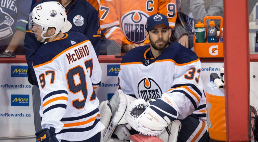 Edmonton-Oilers-goalie-Cam-Talbot,-right,-opens-the-door-for-teammate-Connor-McDavid.