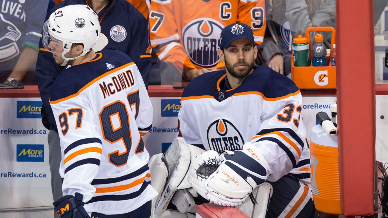 Edmonton-Oilers-goalie-Cam-Talbot,-right,-opens-the-door-for-teammate-Connor-McDavid.