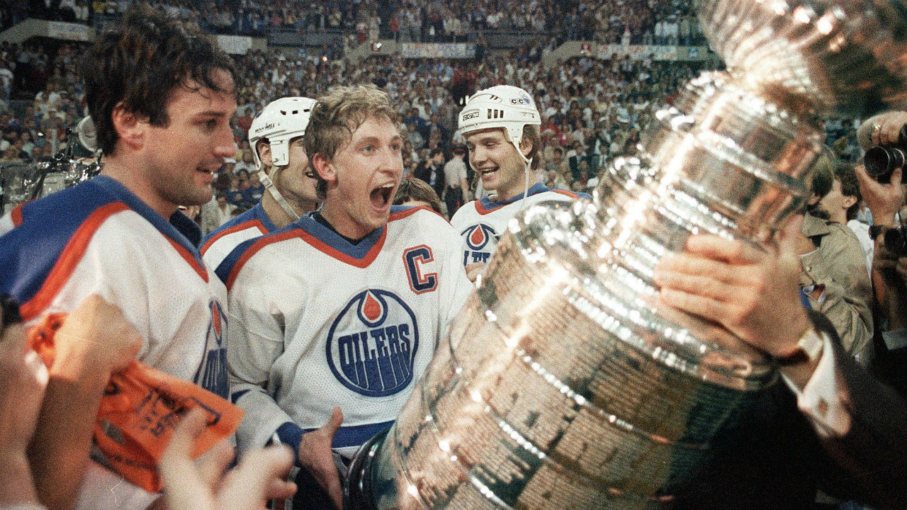 Edmonton-Oilers-captain-Wayne-Gretzky-gets-ready-to-hoist-the-Stanley-Cup-during-the-presentation-in-Edmonton,-Alta.-in-this-May-31,-1985-file-photo.-(CP/Bill-Grimshaw)