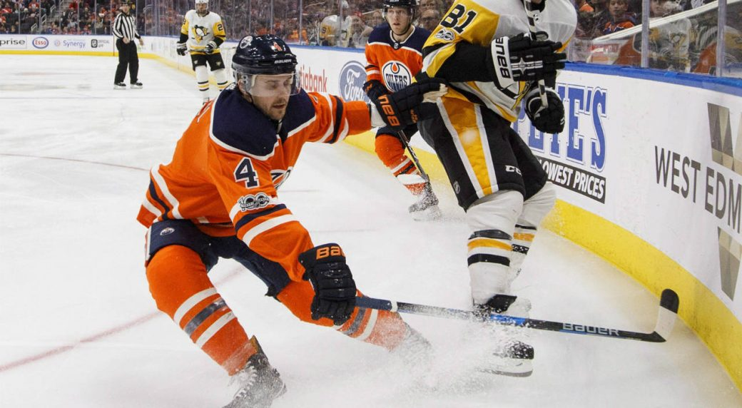 Pittsburgh-Penguins'-Phil-Kessel-(81)-and-Edmonton-Oilers'-Kris-Russell-(4)-battle-for-the-puck-during-first-period-NHL-action-in-Edmonton,-Alta.,-on-Wednesday-November-1,-2017.-(Jason-Franson/CP)