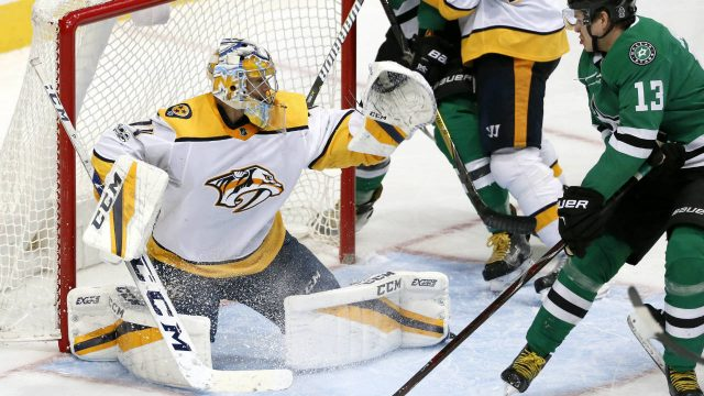 Nashville-Predators-goalie-Juuse-Saros-(74)-defends-against-pressure-from-Dallas-Stars-center-Mattias-Janmark-(13)-as-a-shot-from-the-Star-makes-contact-with-defenseman-Alexei-Emelin-(25)-during-the-third-period-of-an-NHL-hockey-game-Tuesday,-Dec.-5,-2017,-in-Dallas.-(Tony-Gutierrez/AP)