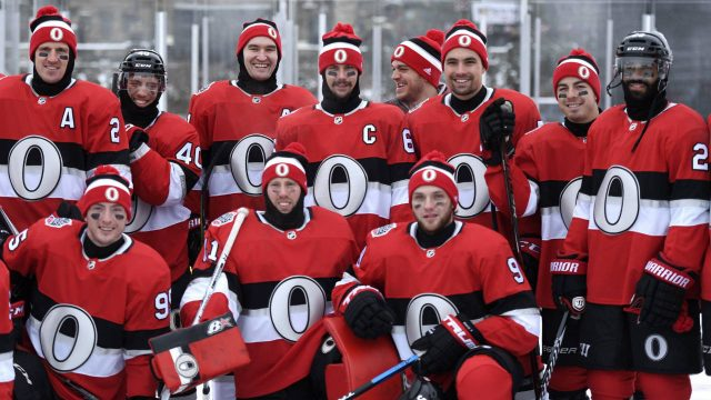 The-Ottawa-Senators,-including-captain-Erik-Karlsson,-pose-for-a-team-photo-on-the-Canada-150-Rink-on-Parliament-Hill,-ahead-of-the-NHL-100-Classic-in-Ottawa-on-Friday,-Dec.-15,-2017.-(Justin-Tang/CP)