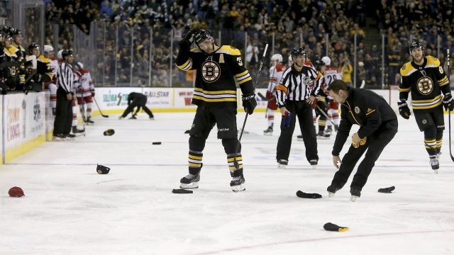 Boston-Bruins-centre-Patrice-Bergeron-(37)-adjusts-his-helmet-as-personnel-clear-hats-from-the-ice-after-Bergeron-scored-his-third-goal-of-the-night,-during-the-second-period-of-an-NHL-hockey-game-against-the-Carolina-Hurricanes-on-Saturday,-Jan.-6,-2018,-in-Boston.-(Mary-Schwalm/AP)