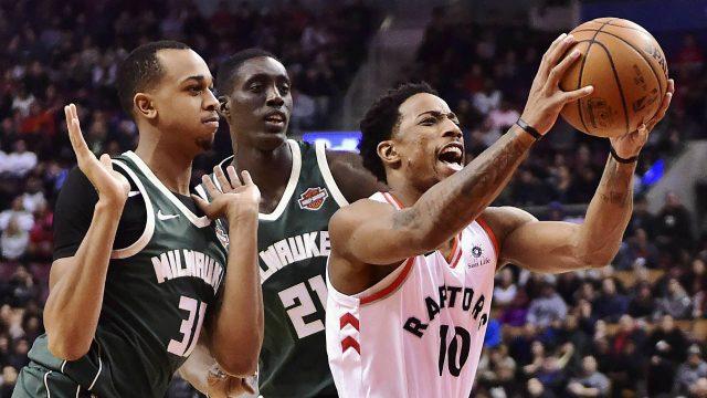 Toronto-Raptors-guard-DeMar-DeRozan-(10)-drives-between-Milwaukee-Bucks-forward-John-Henson-(31)-and-Bucks-guard-Tony-Snell-(21)-during-first-half-NBA-basketball-action-in-Toronto-on-Monday,-January-1,-2018.-(Frank-Gunn/CP)
