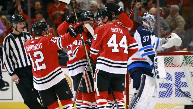 Chicago-Blackhawks-defenceman-Jan-Rutta-(44)-celebrates-with-teammates-after-his-goal-as-Winnipeg-Jets-goaltender-Connor-Hellebuyck-(37)-stands-in-the-net-during-the-second-period-of-an-NHL-hockey-game-Friday,-Jan.-12,-2018,-in-Chicago.-(Jeff-Haynes/AP)