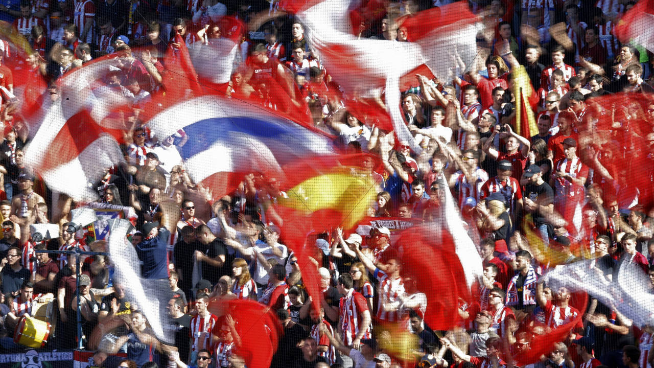 In-a-photo-taken-with-a-slow-shutter-speed,-Atletico-supporters-cheer-and-wave-flags-during-a-La-Liga-soccer-match-between-Atletico-Madrid-and-Sevilla.-(Francisco-Seco/AP)