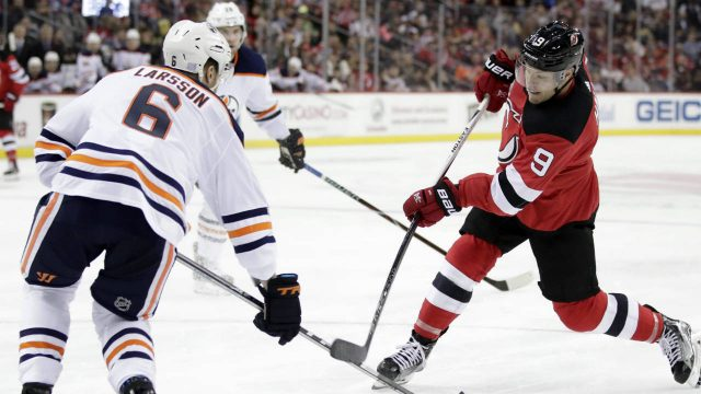 New-Jersey-Devils-left-wing-Taylor-Hall-(9)-takes-a-shot-as-Edmonton-Oilers-defenceman-Adam-Larsson-(6),-of-Sweden,-tries-to-block-it-during-the-second-period-of-an-NHL-hockey-game,-Thursday,-Nov.-9,-2017,-in-Newark,-N.J.-(Julio-Cortez/AP)
