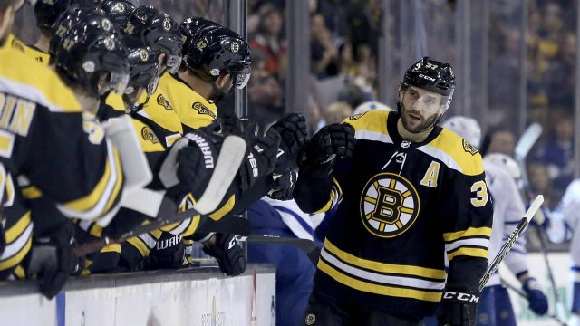 Boston-Bruins-centre-Patrice-Bergeron-(37)-is-congratulated-by-teammates-after-scoring-a-goal-during-the-first-period-of-an-NHL-hockey-game-against-the-Toronto-Maple-Leafs,-Saturday,-Feb.-3,-2018,-in-Boston.-(Mary-Schwalm/AP)