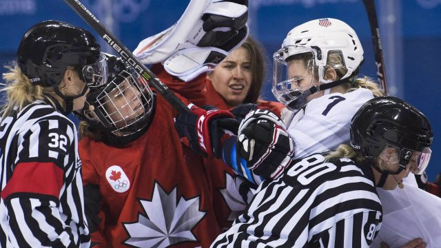 Canada-forward-Marie-Philip-Poulin-(29)-battles-with-United-States-forward-Monique-Lamoureux-Morando-(7)-as-Canada-goaltender-Genevieve-Lacasse,-centre,-had-her-helmet-taken-off-during-third-period-women's-olympic-hockey-action-at-the-2018-Olympic-Winter-Games-in-Gangneung,-South-Korea-on-Thursday,-February-15,-2018.-(Nathan-Denette/CP)