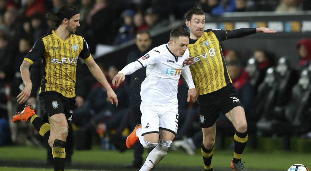 Sheffield-Wednesday's-George-Boyd,-left,-watches-as-Swansea-City's-Connor-Roberts,-centre-and-teammate-David-Jones-battle-for-the-ball,-during-the-FA-Cup,-fifth-round-replay-match-between-Swansea-City-and-Sheffield-Wednesday,-at-the-Liberty-Stadium,-Swansea,-Wales,-Tuesday-Feb.-27,-2018.-(Nick-Potts/PA-via-AP)