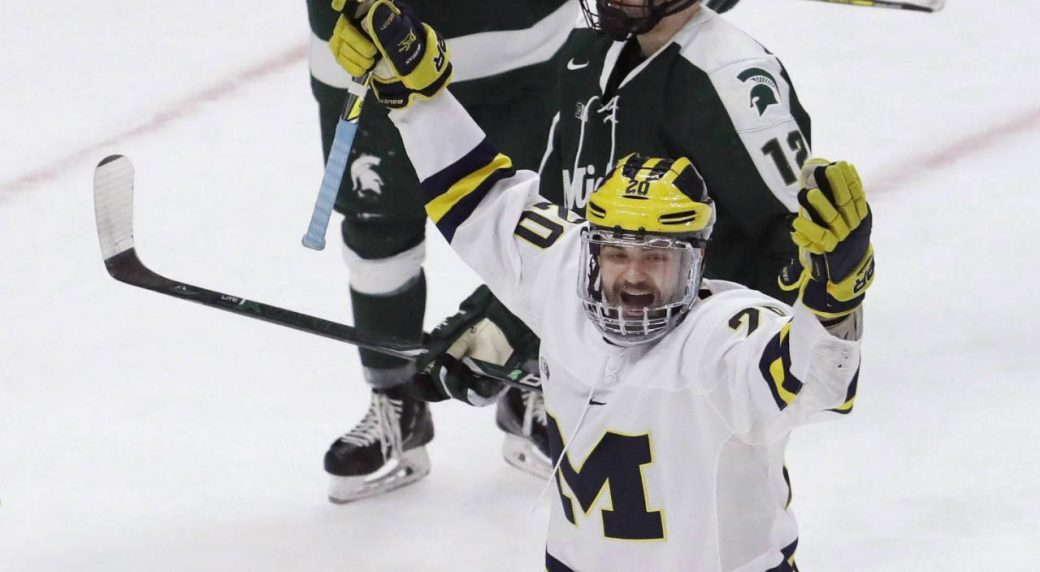Michigan-forward-Cooper-Marody,-right,-reacts-after-his-hat-trick-goal-on-Michigan-State-goaltender-John-Lethemon-(31)-during-the-third-period-of-a-Great-Lakes-Invitational-college-hockey-game,-Tuesday,-Jan.-2,-2018,-in-Detroit.-Michigan-won-6-4.-(Carlos-Osorio/AP)