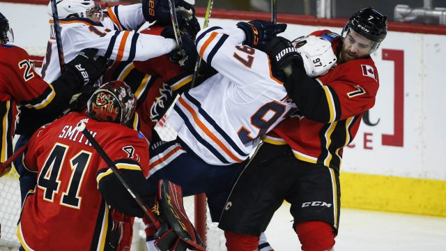 Edmonton-Oilers-centre-Connor-McDavid-(97)-is-hauled-down-by-Calgary-Flames-defenseman-TJ-Brodie-(7)-as-goaltender-Mike-Smith-(41)-looks-on-during-third-period-NHL-hockey-action-in-Calgary,-Tuesday,-March-13,-2018.-(Jeff-McIntosh/CP)