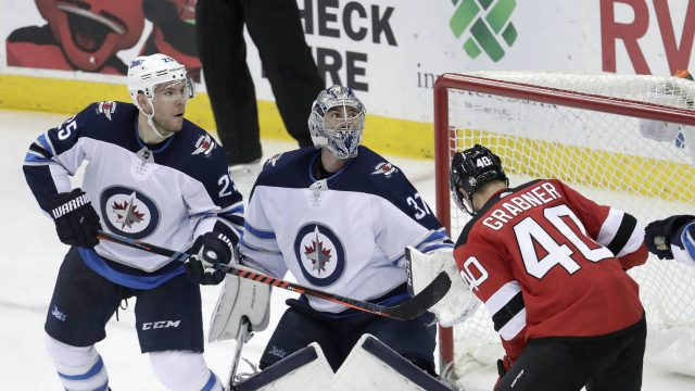 Winnipeg-Jets-goaltender-Connor-Hellebuyck,-centre,-watches-the-puck-kick-up-near-his-net-as-New-Jersey-Devils-right-wing-Michael-Grabner-(40),-of-Austria,-attacks-during-the-second-period-of-an-NHL-hockey-game,-Thursday,-March-8,-2018,-in-Newark,-N.J.-The-Jets-won-3-2.-(Julio-Cortez/AP)