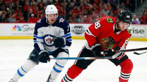 Winnipeg-Jets-defenceman-Dmitry-Kulikov,-left,-battles-with-Chicago-Blackhawks-right-wing-Patrick-Kane