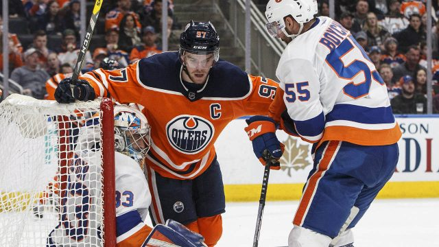 New-York-Islanders'-goalie-Christopher-Gibson-(33)-is-crashed-into-by-Edmonton-Oilers'-Connor-McDavid-(97)-and-Johnny-Boychuk-(55)-during-second-period-NHL-action-in-Edmonton,-Alta.,-on-Thursday-March-8,-2018.-(Jason-Franson/CP)