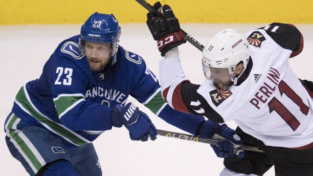 Vancouver-Canucks-defenceman-Alexander-Edler-(23)-fights-for-control-of-the-puck-with-Arizona-Coyotes-left-wing-Brendan-Perlini-(11)-during-second-period-NHL-action-in-Vancouver,-Wednesday,-March-7,-2018.-(Jonathan-Hayward/CP)