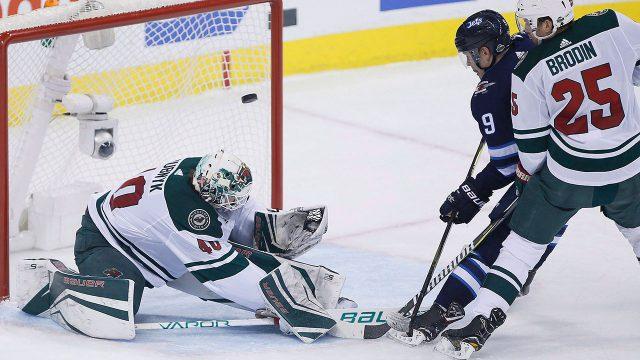 Winnipeg-Jets'-Andrew-Copp-scores-on-Minnesota-Wild's-goaltender-Devan-Dubnyk-as-Jonas-Brodin-defends.