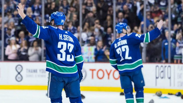 Vancouver-Canucks'-Henrik-Sedin,-left,-and-his-twin-brother-Daniel-Sedin,-both-of-Sweden,-wave-to-the-crowd-after-defeating-the-Arizona-Coyotes-4-3-in-their-last-home-NHL-hockey-game,-in-Vancouver-on-Thursday,-April-5,-2018.-The-brothers-announced-this-week-they-would-be-retiring-from-the-NHL-at-the-end-of-this-season.-(Darryl-Dyck/CP)