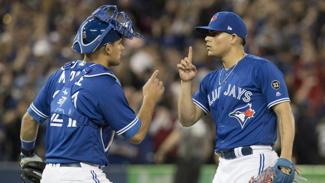 Toronto-Blue-Jays-closer-Roberto-Osuna-and-catcher-Luke-Maile-celebrate-their-American-League-MLB-baseball-win-over-the-New-York-Yankees,-in-Toronto-on-Saturday,-March-31,-2018.-(Fred-Thornhill/CP)