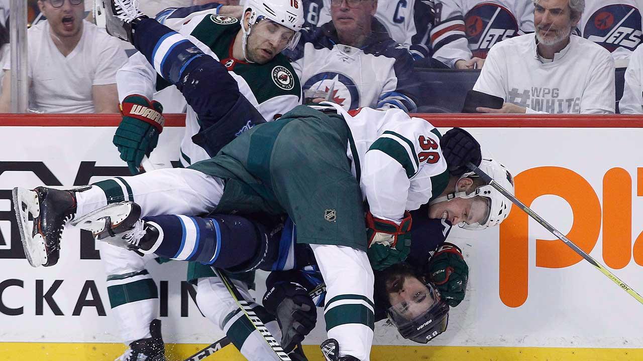 Winnipeg-Jets'-Mathieu-Perreault-gets-checked-by-Minnesota-Wild's-Nick-Seeler-and-Jason-Zucker