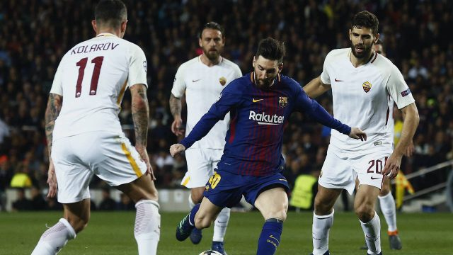 Barcelona's-Lionel-Messi,-centre,-tries-to-score-surrounded-by-Roma's-Aleksandar-Kolarov,-left-and-Roma's-Federico-Fazio-during-a-Champions-League-quarter-final,-first-leg-soccer-match-between-FC-Barcelona-and-Roma-at-the-Camp-Nou-stadium-in-Barcelona,-Spain,-Wednesday,-April-4,-2018.-(Manu-Fernandez/AP)