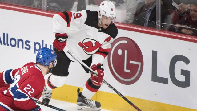 New-Jersey-Devils'-Taylor-Hall-(9)-moves-the-puck-as-Montreal-Canadiens'-Karl-Alzner-defends-during-first-period-NHL-hockey-action-in-Montreal,-Sunday,-April-1,-2018.-(Graham-Hughes/CP)