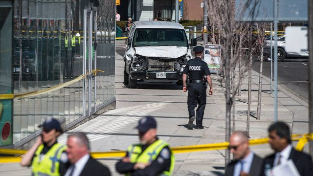 Police-are-seen-near-a-damaged-van-in-Toronto-after-a-van-mounted-a-sidewalk-crashing-into-a-number-of-pedestrians-on-Monday,-April-23,-2018.-(Aaron-Vincent-Elkaim/CP)